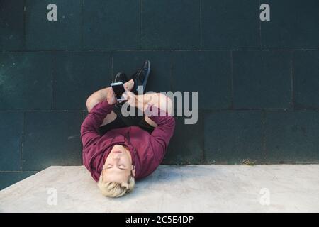 Jeune homme caucasien en vêtements de sport assis sur le sol, se reposant après l'entraînement et écoutant de la musique sur des écouteurs. Vue de dessus Banque D'Images