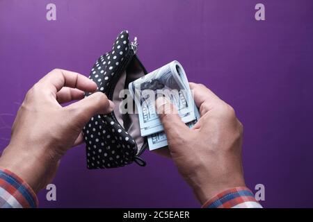 personne mettant de l'argent dans un portefeuille Banque D'Images