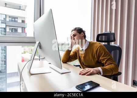 Homme d'affaires frustré assis à la réception avec la main dans le bureau Banque D'Images