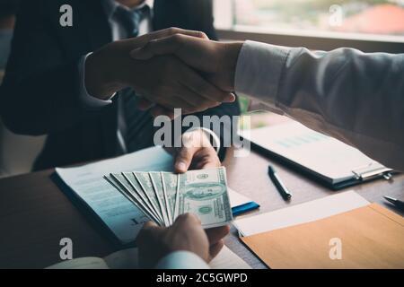 Deux hommes d'affaires se secouent la main tandis qu'un homme donne de l'argent et reçoit de l'argent sale dans la salle de bureau avec le concept de corruption.