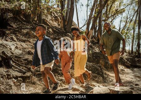Une jeune famille profite de ses vacances dans un parc national. Famille africaine marchant sur un sentier de montagne et s'amusant.