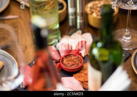 Saucisse savoureuse avec tomate et sauce avec bouteilles de vin Banque D'Images
