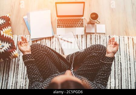 Femme d'affaires vêtue de pyjama méditant avec le café du matin avec des palmiers Gyan Mudra.sur le bureau d'étage avec ordinateur portable, les papiers vue de dessus. Distance
