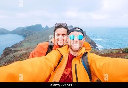 Souriant, les routards se font un portrait de selfie en faisant de la randonnée et en profitant de la vue sur l'océan Atlantique sur la péninsule de Ponta de Sao Lourenço