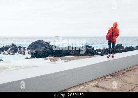 Femme touristique avec sac à dos profitant de la puissance de l'océan regardant les vagues surf dans les piscines naturelles de Porto Moniz, île de Madère, Portugal.