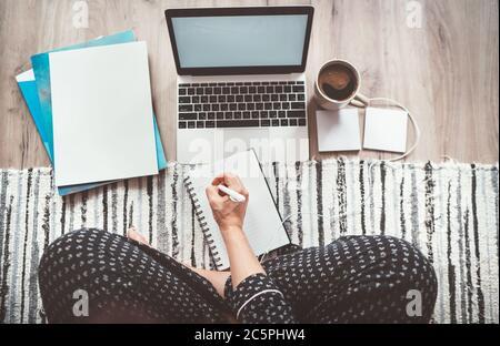 Femme d'affaires habillée pyjama écrivant plan de jour appréciant le café du matin sur le salon bureau au sol avec ordinateur portable, des journaux et d'autres choses vue du dessus shot.D.