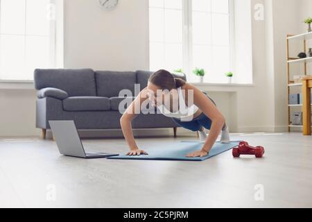 Belle fille de coupe dans les vêtements de sport regarder la vidéo d'entraînement en ligne et faire des exercices de poussée ou de planche à la maison
