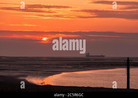 Vue sur la mer depuis Fleetwood sur la côte du Lancashire avec un bateau passant dans la mer irlandaise au coucher du soleil