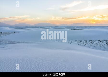 Parc national des dunes de sable blanc classé monument avec motifs de sable ondule sur les dunes du Nouveau-Mexique avec le soleil sur l'horizon au coucher du soleil et la silhouette des montagnes Banque D'Images