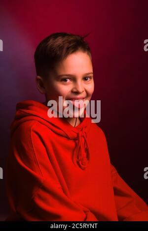 Portrait studio d'un garçon aux cheveux sombres, sur fond marron, dans une veste à capuche rouge. Émotions positives, sourire sur votre visage Banque D'Images