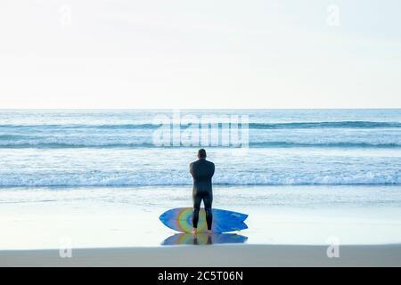 Un surfeur mâle contemplant l'océan à la Jolla, Californie Banque D'Images