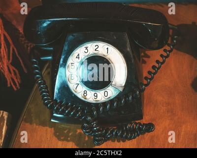 Gros plan photo d'un ancien téléphone noir sur une table en bois Banque D'Images