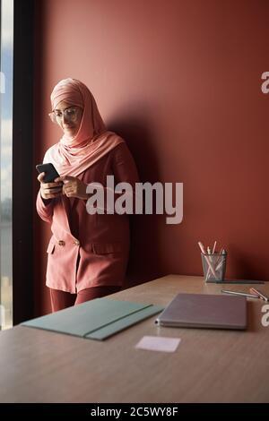 Portrait vertical de la jeune femme d'affaires musulmane utilisant un smartphone tout en se tenant contre le mur rouge dans le bureau, espace de copie Banque D'Images