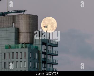 Cork, Cork, Irlande. 06e juillet 2020. Une pleine lune descend derrière le Tricolore irlandais qui flotte au-dessus de l'Elysian, le deuxième plus haut bâtiment d'Irlande à Cork, en Irlande. - crédit; David Creedon / Alamy Live News Banque D'Images