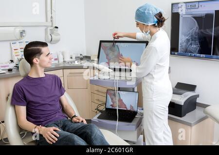 Femme en uniforme médical pointant vers la cavité de la dent sur l'acquisition 3D à sourire client mâle pendant le travail dans la clinique moderne.