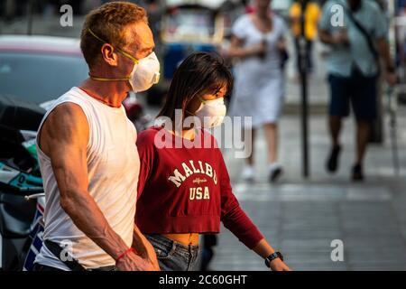 Couple marchant dans la rue avec masque facial pendant la pandémie de Covid 19, Bangkok, Thaïlande