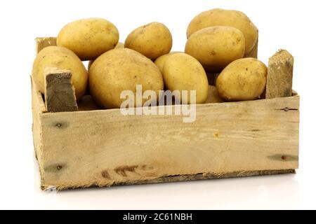 bouquet de pommes de terre fraîchement récoltées dans une boîte en bois et quelques-unes à côté sur fond blanc Banque D'Images