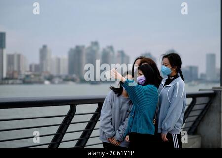 Plusieurs jeunes filles portant un masque facial pour prévenir le coronavirus, prenant le selfie au bund à Shanghai en Chine