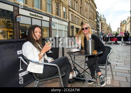 Glasgow, Écosse, Royaume-Uni. 6 juillet 2020. Photo : deux femmes buvant du vin blanc dans le style Mile de Glasgow, Buchanan Street. Dès aujourd'hui, des pubs, des bars, des cafés et des restaurants en Angleterre, en Écosse et en Irlande du Nord accueillent des clients pour la première fois depuis le début du confinement en mars. Crédit : Colin Fisher/Alay Live News Banque D'Images