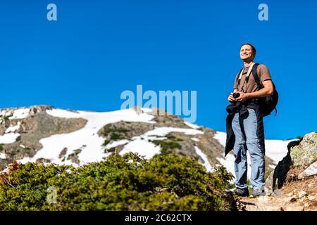Homme debout avec caméra au sommet du sentier du lac Linkins sur le col de l'indépendance dans les montagnes rocheuses près d'Aspen, Colorado, au début de l'été 2019 avec s Banque D'Images