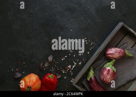 Variétés d'aubergines dans un bol noir sur fond d'ardoise sombre. Vue en hauteur.