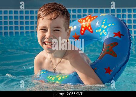 Un petit garçon mignon s'amuser dehors dans le jardin d'été. Un garçon souriant joue et s'amuse dans la piscine pour enfants par beau temps d'été. Activités avec les enfants. Banque D'Images