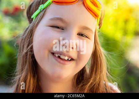 Portrait d'une belle petite fille qui se smille avec des lunettes de protection pour la piscine. Activités avec enfants à l'extérieur. L'été s'amuser. Copier l'espace. Banque D'Images