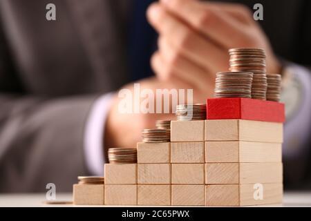 Pile de pièces de monnaie sur des cubes en bois en forme d'escalier Banque D'Images