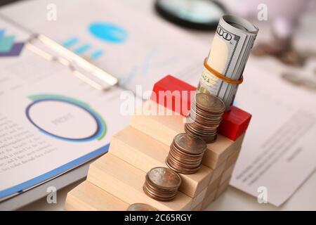 Cube en bois avec pièces en or et rapport sur la table Banque D'Images