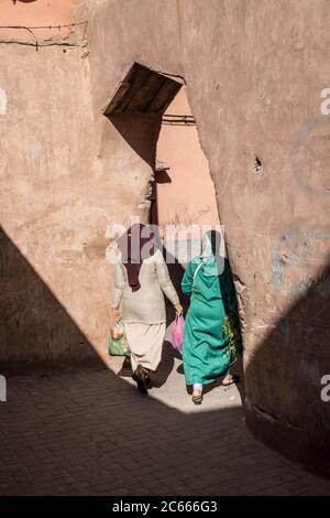 Deux femmes dans un caftan marchant dans une arcade orientale, Marrakech, Maroc