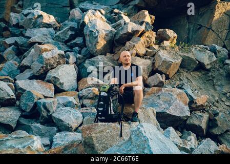 un voyageur repose sur une pierre et regarde le bord autour de lui. Un touriste se trouve sur le fond du rocher en été