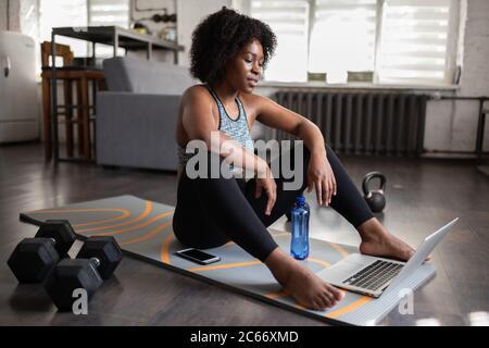 Femme ethnique fatiguée assise sur un tapis et regardant la vidéo pendant la pause dans l'entraînement en ligne