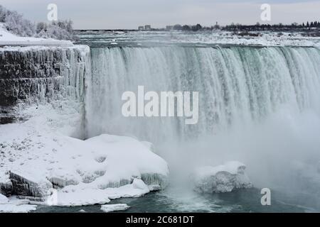 Une partie des chutes du fer à cheval en hiver. Les glaces pendent de la face rocheuse près de la cascade. Arbres et rochers couverts de neige. Chutes du Niagara. Banque D'Images