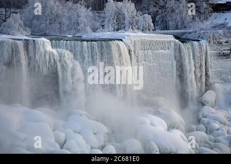 Chutes américaines et chutes de veau de mariée en hiver. Arbres et rochers gelés et neige au sol. Brume qui s'élève des chutes. Chutes du Niagara.