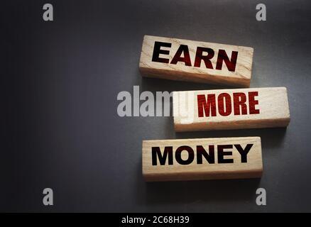 Gagnez plus d'argent écrit sur des blocs de bois sur noir. Concept de carrière professionnelle
