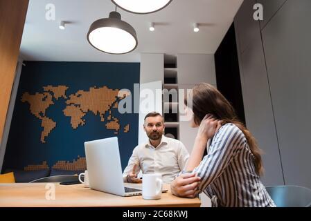 Homme assis au bureau avec un ordinateur portable et parlant à une femme