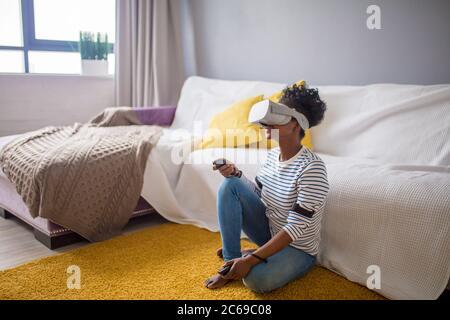 Happy casual african american female student en bleu dépouillé t-shirt acquérir de l'expérience à l'aide de lunettes casque VR de la réalité virtuelle, assis sur yello Banque D'Images
