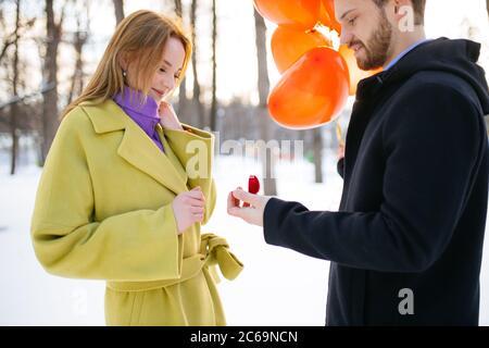 romantique caucasien barbu homme en manteau faisant la proposition de mariage à sa petite amie dans la rue d'hiver. homme tenir une petite boîte rouge floqué et l'air rouge ba