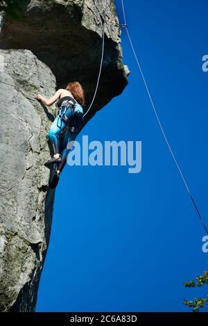 Photo verticale d'une femme grimpante sur une falaise, portant des leggings bleus et un haut noir dans un harnais de sécurité par temps ensoleillé, ciel bleu clair sur fond. Vue en angle bas Banque D'Images