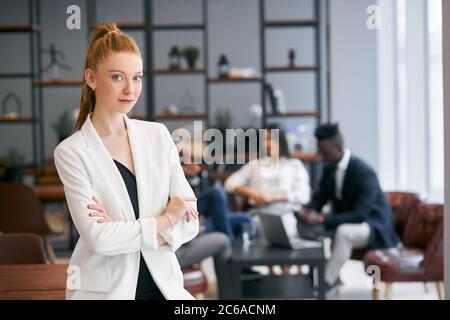 Belle femme avec un cheveu rouge regardant la caméra, posant à la caméra. Groupe international de partenaires commerciaux