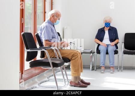 Femme et homme âgés assis avec un masque facial dans une salle d'attente lumineuse d'un hôpital ou d'un bureau Banque D'Images