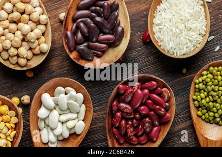Cuillères en bois avec grains et haricots sur table en bois Banque D'Images