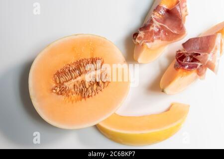 Vue de dessus de la moitié de melon à côté de quelques tranches de jambon fin sur le dessus d'eux sur un fond clair. Concept de cuisine et de mode de vie savoureux. Banque D'Images