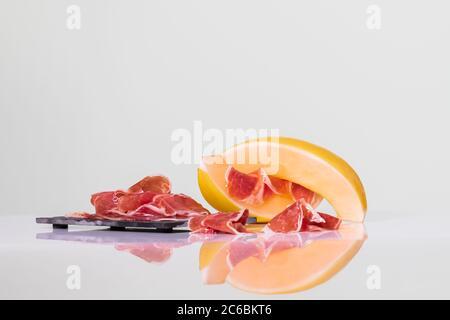 Fines tranches de jambon sur une assiette foncée à côté des tranches de melon avec quelques tranches de jambon plus séchées sur un fond clair. Concept de cuisine et de mode de vie savoureux. Banque D'Images