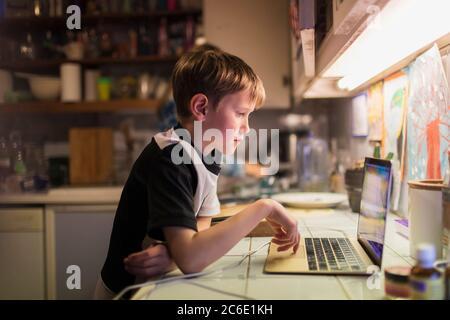 Garçon faisant ses devoirs à l'ordinateur portable sur le comptoir de la cuisine Banque D'Images