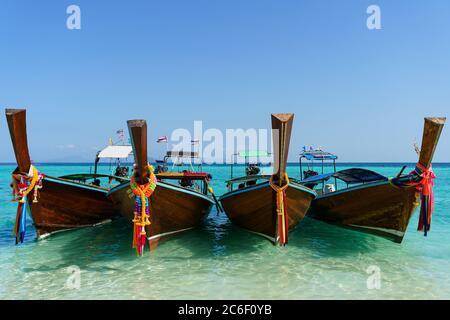 Divers bateaux asiatiques sur l'eau turquoise le jour ensoleillé et le ciel bleu