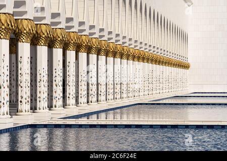 Vue sur les colonnes blanches de la mosquée d'Abou Dhabi, reflétée dans l'eau de la piscine par une journée ensoleillée. Banque D'Images