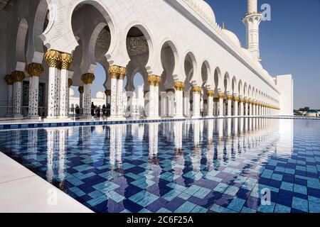 Vue sur les colonnes blanches de la mosquée d'Abu Dhabi, reflétée dans l'eau de la piscine, par une journée ensoleillée avec un ciel bleu Banque D'Images