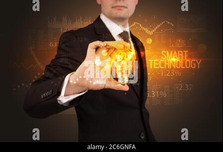 Homme d'affaires tenant une ampoule avec inscription INTELLIGENTE À LA TECHNOLOGIE, Business Technology concept Banque D'Images