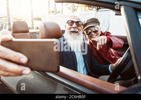 Couple senior heureux prenant selfie sur nouvelle voiture convertible - personnes d'âge mûr ayant plaisir dans le cabriolet ensemble pendant les vacances de voyage Banque D'Images